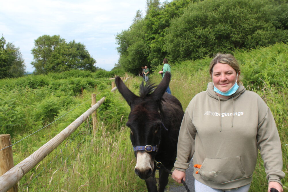 A woman walking with a donkey in the country field. - ©Swansea Community Farm