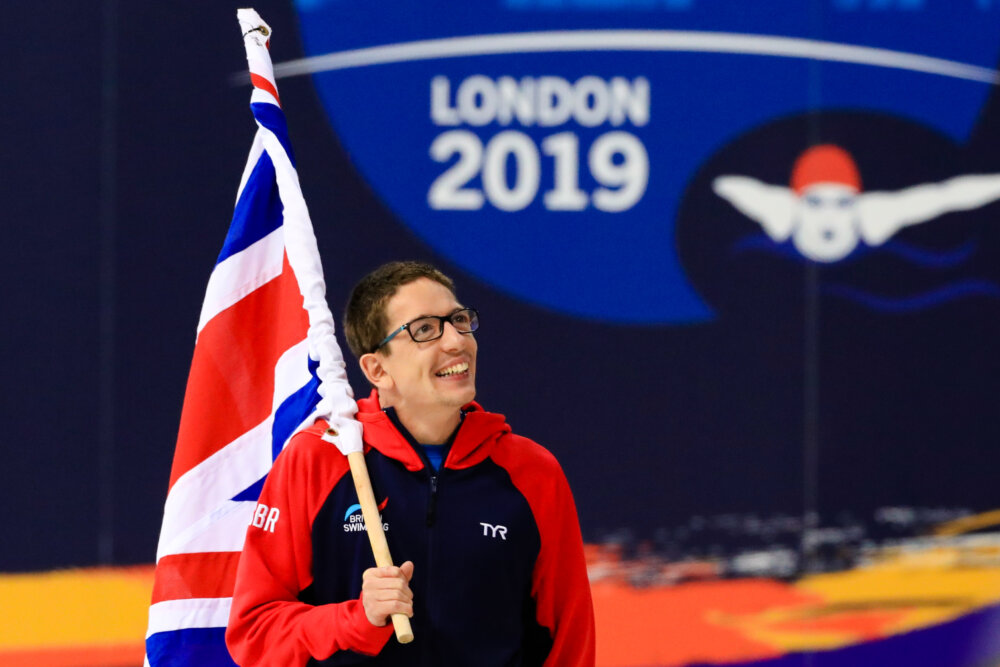 Scott Quin, Brititsh paralympic swimmer, holding the Great Britain's flag in a sport event.