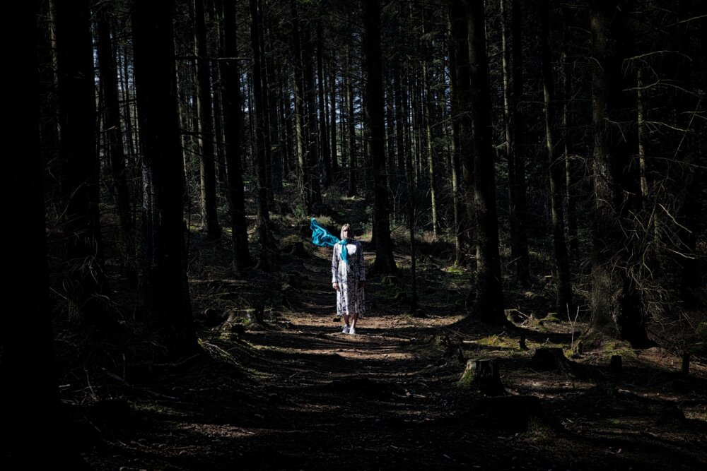 """A woman walking in the woods alone from the postr of the """"You're not alone"""" for the Baby Loss Awareness Week"""